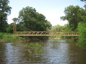 A fully customized 76 foot suspension bridge across the pond.